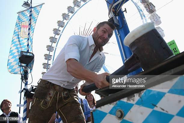 Martin Tomczyk enjoys the high striker during the BMW Wiesn Sport Stammtisch Oktoberfest 2013 at Kaefers Wiesn Schaenke Theresienwiese on September...