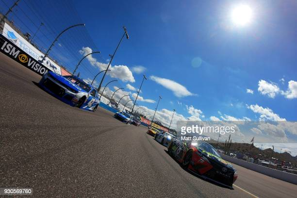 Martin Truex Jr driver of the 5hour Energy/Bass Pro Shops Toyota and Kyle Larson driver of the Credit One Bank Chevrolet lead the field during pace...