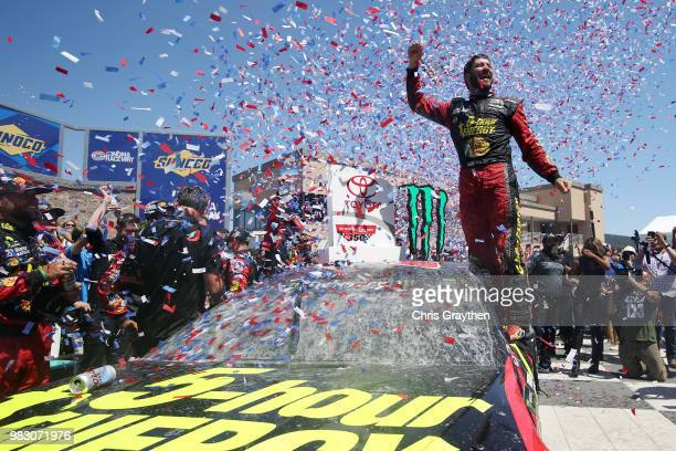 Martin Truex Jr driver of the 5hour ENERGY/Bass Pro Shops Toyota celebrates in victory lane after winning the Monster Energy NASCAR Cup Series...