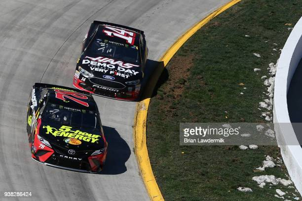 Martin Truex Jr driver of the 5hour ENERGY/Bass Pro Shops Toyota leads Clint Bowyer driver of the Haas Automation Demo Day Ford during the weather...