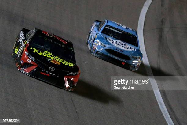 Martin Truex Jr driver of the 5hour ENERGY/Bass Pro Shops Toyota leads Kevin Harvick driver of the Busch Light Ford during the Monster Energy NASCAR...