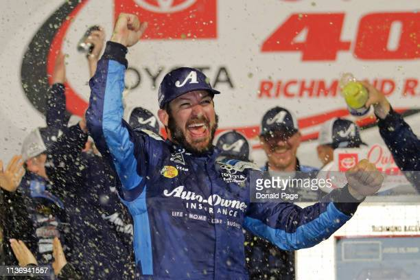 Martin Truex Jr driver of the Auto Owners Insurance Toyota celebrates in Victory Lane after winning the Monster Energy NASCAR Cup Series Toyota...