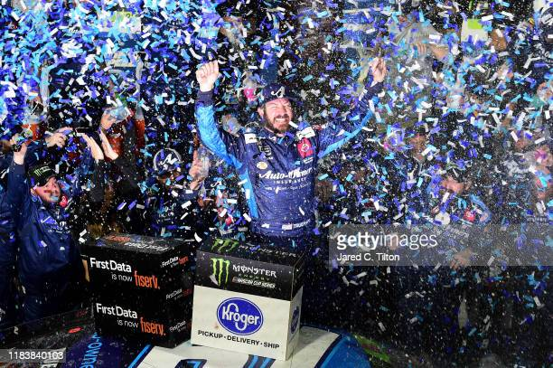 Martin Truex Jr driver of the Auto Owners Insurance Toyota celebrates in Victory Lane after winning the Monster Energy NASCAR Cup Series First Data...