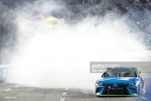 Martin Truex Jr driver of the Auto Owners Insurance Toyota celebrates with a burnout after winning the Monster Energy NASCAR Cup Series First Data...