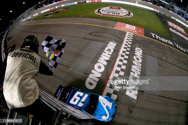 Martin Truex Jr driver of the Auto Owners Insurance Toyota takes the checkered flag to win the Monster Energy NASCAR Cup Series Toyota Owners 400 at...