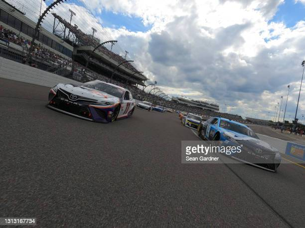 Martin Truex Jr., driver of the Auto-Owners Insurance Toyota, and Denny Hamlin, driver of the FedEx Express Toyota, lead the field on a pace lap...