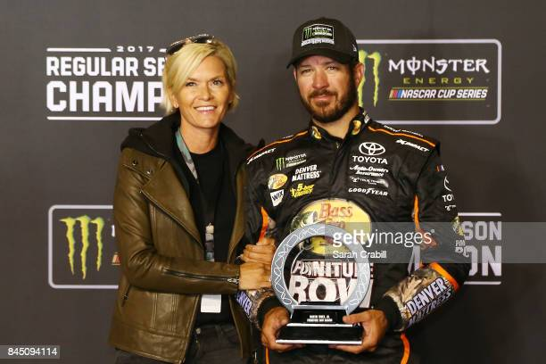Martin Truex Jr driver of the AutoOwners Insurance Toyota and his girlfriend Sherry Pollex pose for a photo opportunity in Victory Lane with the...