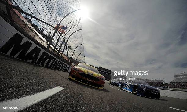 Martin Truex Jr driver of the AutoOwners Insurance Toyota and Joey Logano driver of the Shell Pennzoil Ford lead the field under caution prior to the...