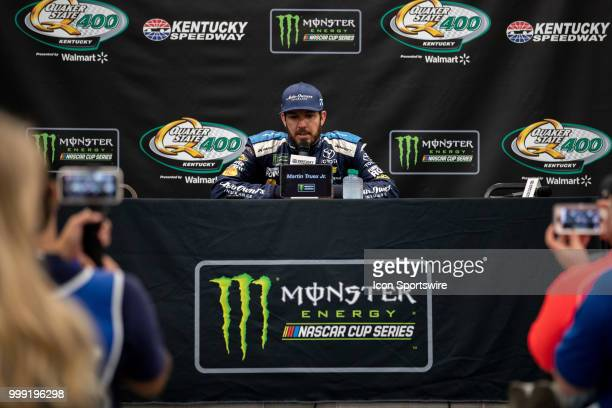 Martin Truex Jr driver of the AutoOwners Insurance Toyota answers questions for the media after winning the Monster Energy NASCAR Cup Series Quaker...