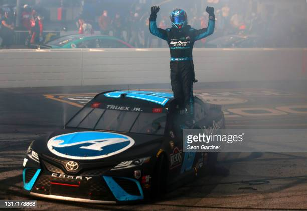 Martin Truex Jr., driver of the Auto-Owners Insurance Toyota, celebrates after winning the NASCAR Cup Series Goodyear 400 at Darlington Raceway on...