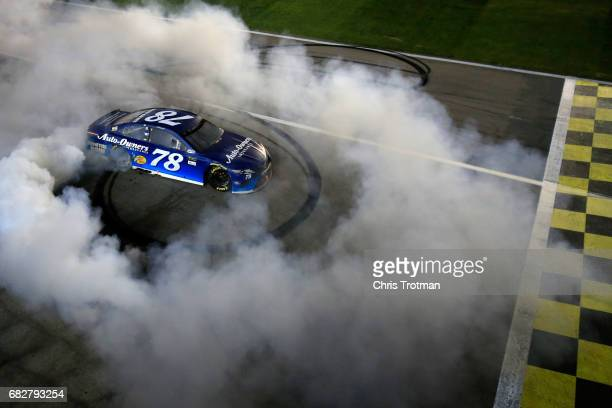 Martin Truex Jr driver of the AutoOwners Insurance Toyota celebrates with a burnout after winning the Monster Energy NASCAR Cup Series Go Bowling 400...