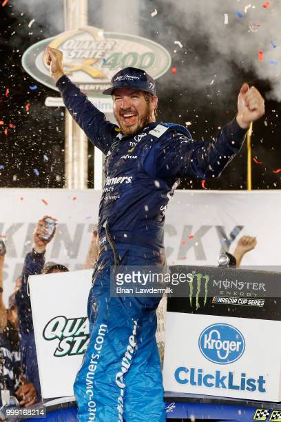 Martin Truex Jr driver of the AutoOwners Insurance Toyota celebrates in Victory Lane after winning the Monster Energy NASCAR Cup Series Quaker State...
