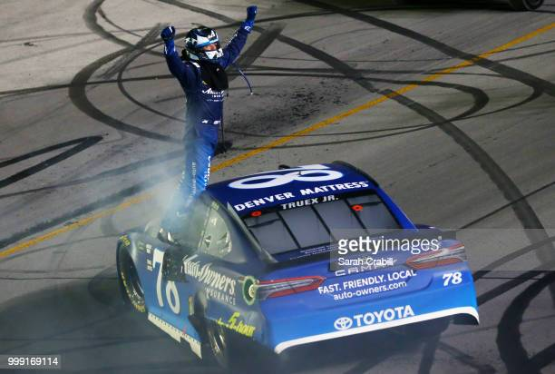 Martin Truex Jr driver of the AutoOwners Insurance Toyota celebrates winning the Monster Energy NASCAR Cup Series Quaker State 400 presented by...