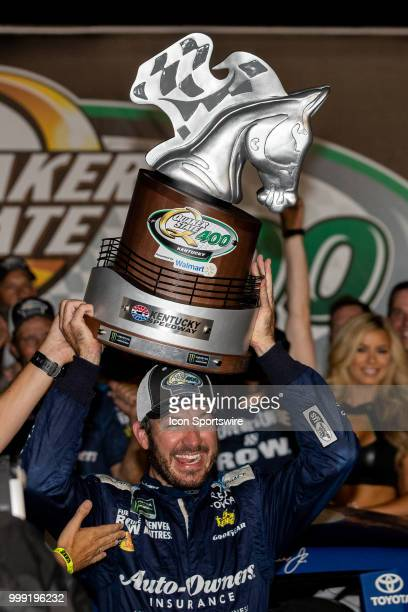 Martin Truex Jr driver of the AutoOwners Insurance Toyota celebrates with the trophy after winning the Monster Energy NASCAR Cup Series Quaker State...