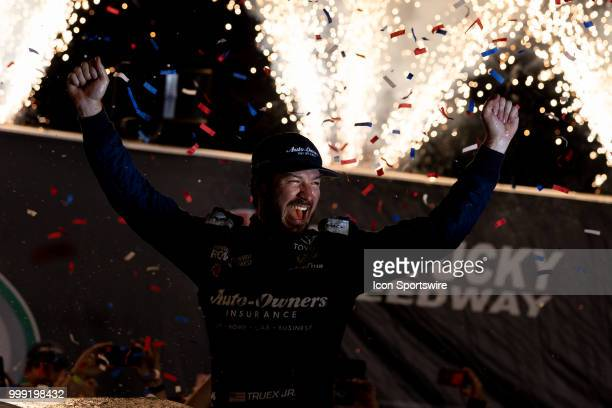 Martin Truex Jr driver of the AutoOwners Insurance Toyota celebrates after winning the Monster Energy NASCAR Cup Series Quaker State 400 presented by...