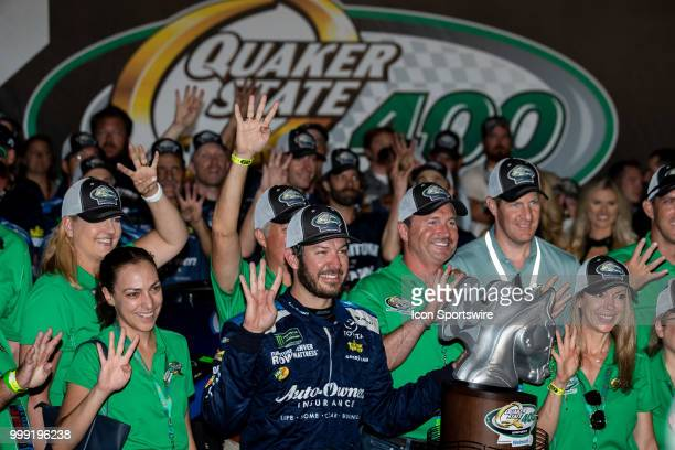 Martin Truex Jr driver of the AutoOwners Insurance Toyota holds up four fingers to signify his four wins at Kentucky Speedway in the Monster Energy...