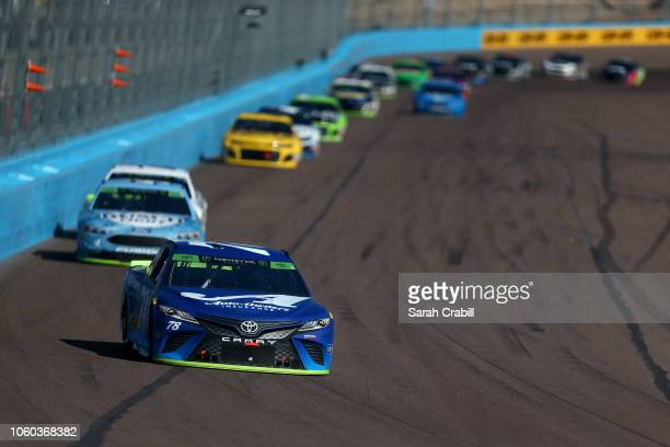 Martin Truex Jr driver of the AutoOwners Insurance Toyota leads a group of cars during the Monster Energy NASCAR Cup Series CanAm 500 at ISM Raceway...
