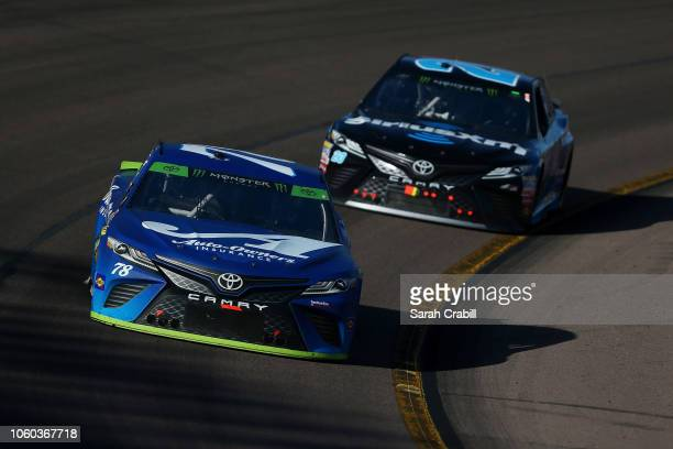Martin Truex Jr driver of the AutoOwners Insurance Toyota leads Erik Jones driver of the Sirius XM Toyota during the Monster Energy NASCAR Cup Series...