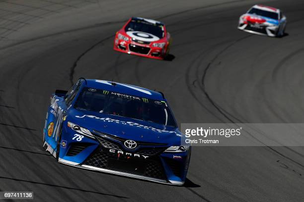 Martin Truex Jr driver of the AutoOwners Insurance Toyota leads Kyle Larson driver of the Cars 3/Target Chevrolet and Kyle Busch driver of the MM's...