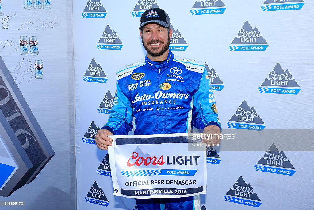 Martin Truex Jr, driver of the #78 Auto-Owners Insurance Toyota, poses with the Coors Light Pole Award after qualifying in the pole position for the NASCAR Sprint Cup Series Goody's Fast Relief 500 at Martinsville Speedway on October 28, 2016 in Martinsville, Virginia.