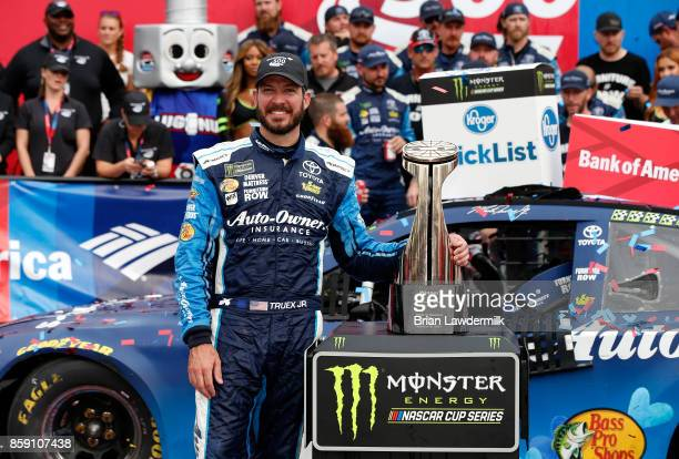 Martin Truex Jr driver of the AutoOwners Insurance Toyota poses with the trophy in Victory Lane after winning the Monster Energy NASCAR Cup Series...