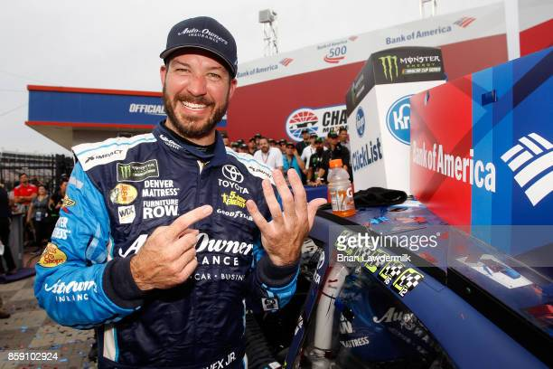 Martin Truex Jr driver of the AutoOwners Insurance Toyota puts the winner's sticker on his car in Victory Lane after winning the Monster Energy...