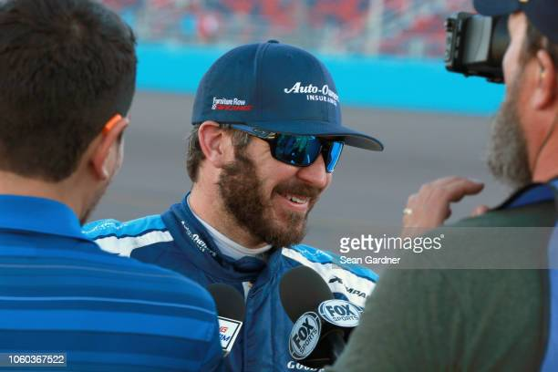 Martin Truex Jr driver of the AutoOwners Insurance Toyota speaks with the media following the Monster Energy NASCAR Cup Series CanAm 500 at ISM...