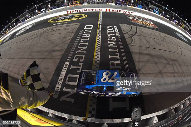 Martin Truex Jr driver of the AutoOwners Insurance Toyota takes the checkered flag to win the NASCAR Sprint Cup Series Bojangles' Southern 500 at...