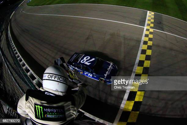 Martin Truex Jr driver of the AutoOwners Insurance Toyota takes the checkered flag to win the Monster Energy NASCAR Cup Series Go Bowling 400 at...
