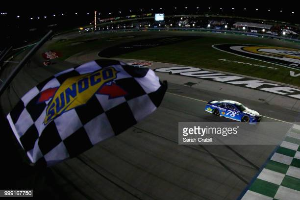 Martin Truex Jr., driver of the Auto-Owners Insurance Toyota, takes the checkered flag to win the Monster Energy NASCAR Cup Series Quaker State 400...