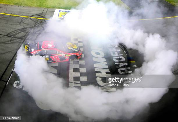 Martin Truex Jr driver of the Bass Pro Shops Toyota celebrates with a burnout after winning the Monster Energy NASCAR Cup Series Federated Auto Parts...