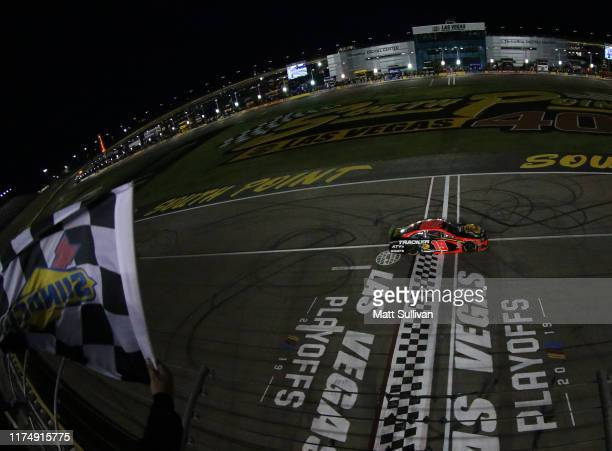 Martin Truex Jr driver of the Bass Pro Shops Toyota crosses the finish line to win the Monster Energy NASCAR Cup Series South Point 400 at Las Vegas...