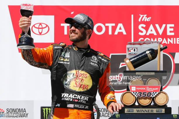 Martin Truex Jr driver of the Bass Pro Shops Toyota poses with the trophy in Victory Lane after winning the Monster Energy NASCAR Cup Series...
