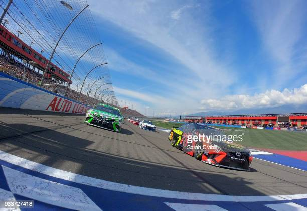 Martin Truex Jr driver of the Bass Pro Shops/5hour ENERGY Toyota and Kyle Busch driver of the Interstate Batteries Toyota lead the field to green for...