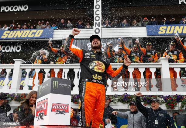 Martin Truex Jr driver of the Bass Pro Shops/5hour ENERGY Toyota celebrates in Victory Lane after winning the Monster Energy NASCAR Cup Series Pocono...