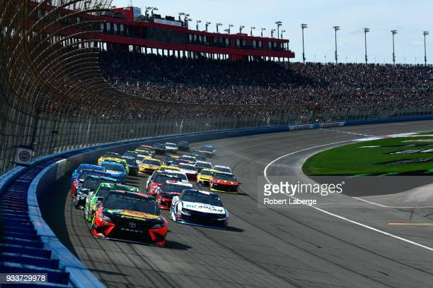 Martin Truex Jr driver of the Bass Pro Shops/5hour ENERGY Toyota leads the field on lap one during the Monster Energy NASCAR Cup Series Auto Club 400...