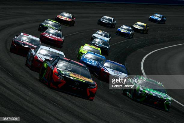 Martin Truex Jr driver of the Bass Pro Shops/5hour ENERGY Toyota leads Kyle Busch driver of the Interstate Batteries Toyota during the Monster Energy...
