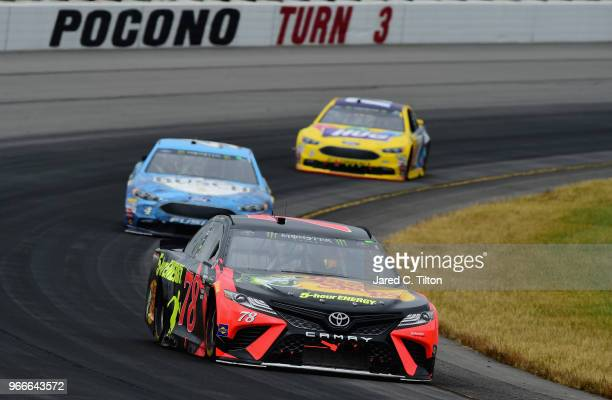 Martin Truex Jr driver of the Bass Pro Shops/5hour ENERGY Toyota leads Kevin Harvick driver of the Busch Beer Ford and Ricky Stenhouse Jr driver of...