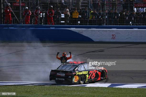 Martin Truex Jr driver of the Bass Pro Shops/5hour ENERGY Toyota celebrates after winning the Monster Energy NASCAR Cup Series Auto Club 400 at Auto...