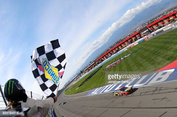 Martin Truex Jr driver of the Bass Pro Shops/5hour ENERGY Toyota takes the checkered flag to win the Monster Energy NASCAR Cup Series Auto Club 400...