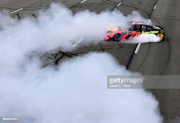 Martin Truex Jr driver of the Bass Pro Shops/5hour ENERGY Toyota celebrates with a burnout after winning the Monster Energy NASCAR Cup Series Pocono...
