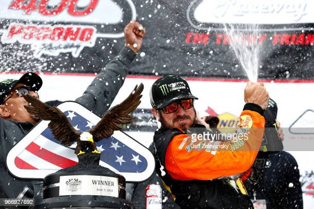 Martin Truex Jr driver of the Bass Pro Shops/5hour ENERGY Toyota celebrates with champagne in Victory Lane after winning the Monster Energy NASCAR...