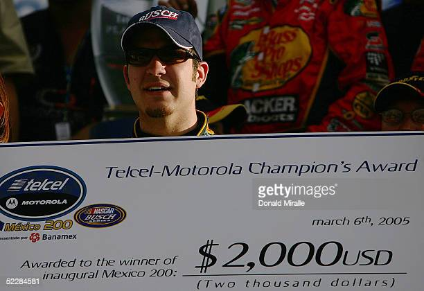Martin Truex Jr., driver of the Bass Pro ShopsChevrolet Monte Carlo, holds the winner's check after his victory during the Telcel Mexico 200 Nascar...