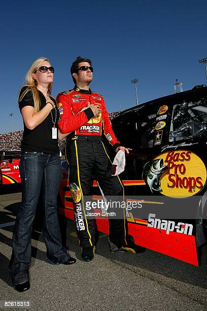 Martin Truex Jr driver of the Bass Pro Shops/Tracker Boats Chevrolet and guest Sherry Pollex stand on the grid during th national anthem for the...