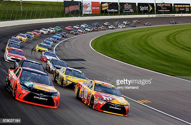 Martin Truex Jr driver of the Bass Pro Shops/TRACKER Boats Toyota Toyota leads a pack of cars during the NASCAR Sprint Cup Series Go Bowling 400 at...