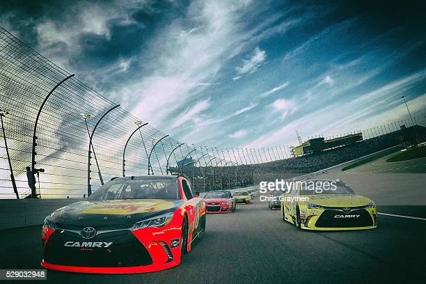 Martin Truex Jr driver of the Bass Pro Shops/TRACKER Boats Toyota Toyota and Matt Kenseth driver of the Dollar General Toyota lead the field at the...