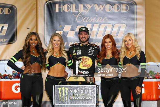 Martin Truex Jr driver of the Bass Pro Shops/Tracker Boats Toyota and the Monster Girls pose for a photo with the trophy in Victory Lane after...