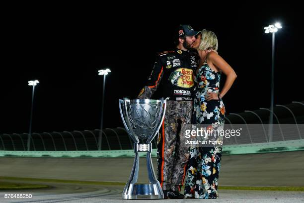 Martin Truex Jr driver of the Bass Pro Shops/Tracker Boats Toyota and Sherry Pollex pose with the Monster Energy NASCAR Cup Series championship...