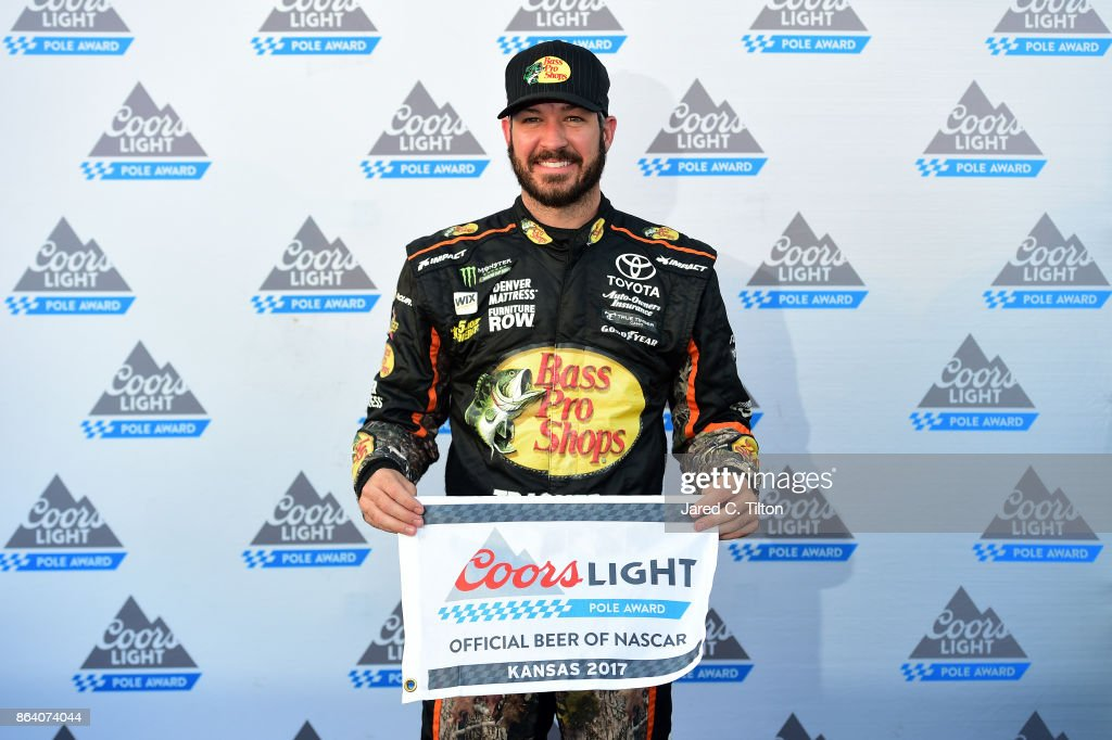 Martin Truex Jr., driver of the #78 Bass Pro Shops/Tracker Boats Toyota, poses for a photo after winning the pole award during qualifying for the Monster Energy NASCAR Cup Series Hollywood Casino 400 at Kansas Speedway on October 20, 2017 in Kansas City, Kansas.