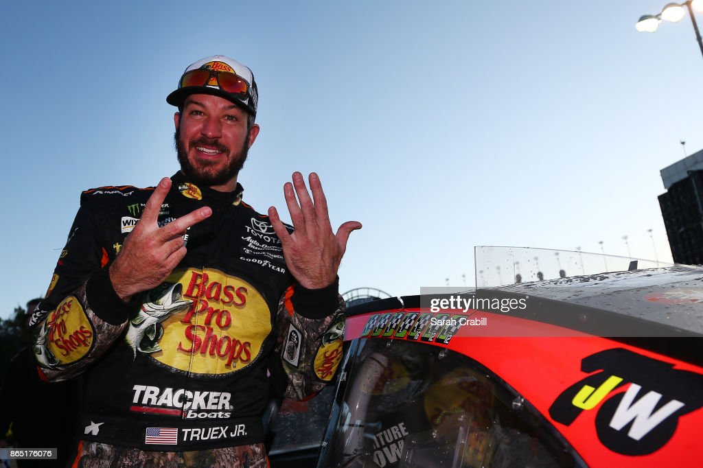 Martin Truex Jr., driver of the #78 Bass Pro Shops/Tracker Boats Toyota, poses for a photo with the winner's decal in Victory Lane after winning the Monster Energy NASCAR Cup Series Hollywood Casino 400 at Kansas Speedway on October 22, 2017 in Kansas City, Kansas.